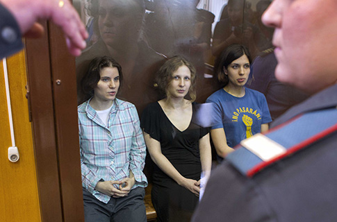 Feminist punk group Pussy Riot members sit in a glass cage at a court room in Moscow Friday. (AP Photo/Misha Japaridze)