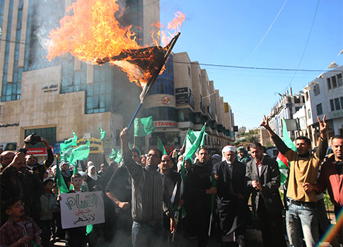 Palestinian Hamas supporters burning the Israeli flag / AP