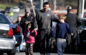 Parents leave a staging area after being reunited with their children following a shooting at the Sandy Hook Elementary School in Newtown, Conn. (AP)
