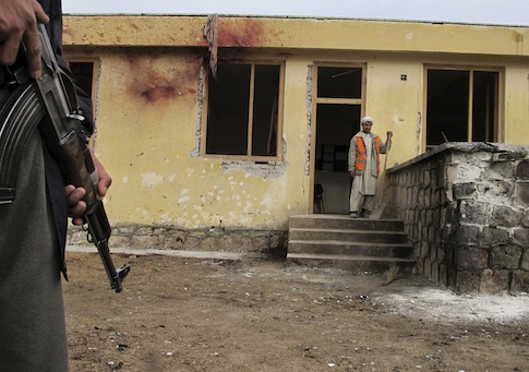 Afghan police officer stands guard at the site of an explosion in the Imam Sahib district of Kunduz / AP