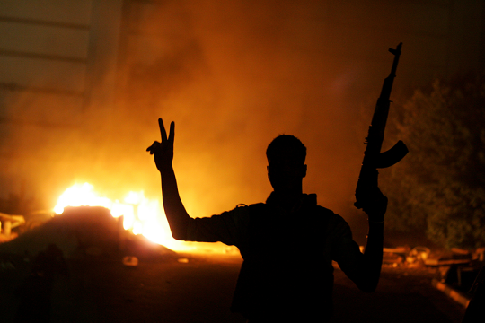 An armed libyan man flashes the victory sign in front of a fire at the hardline Islamist group Ansar el-Sharia headquarters on Sept. 21, 2012 in Benghazi. (Getty)