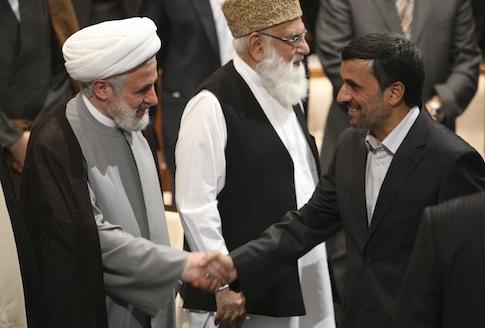 Iranian President Mahmoud Ahmadinejad shakes hands with deputy leader of Lebanese Hezbollah / AP