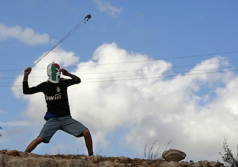 A Palestinian protester hurls a stone at Israeli security forces in Nabi Saleh / AP