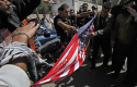 Palestinians rip an American flag during a protest against the visit of President Barack Obama / AP