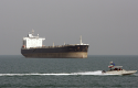 An Iranian Revolutionary Guard speedboat escorts a passenger ship with oil tanker in background / AP
