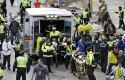 Medical workers aid injured people at the finish line of the 2013 Boston Marathon / AP
