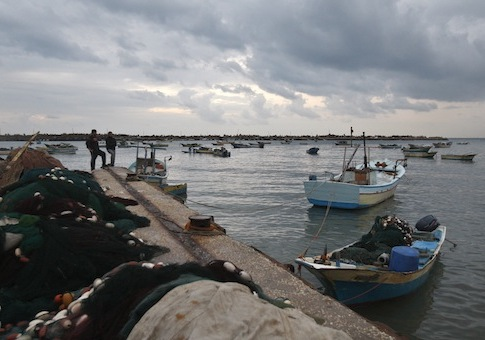 Fishermen stand at the Gaza seaport, in Gaza City / AP