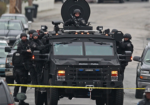Police in tactical gear arrive on an armored police vehicle search for Dzhokhar Tsarnaev / AP