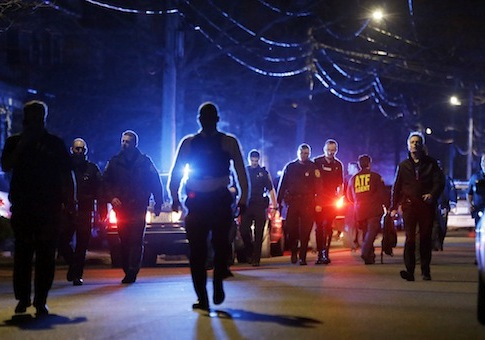 Police officers walk near a crime scene in Watertown, Mass. on April 19 / AP