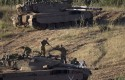 Israeli soldiers work on top of a tank in a position in the Israeli controlled Golan Heights / AP