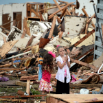 Two girls stand in rubble after a tornado struck Moore, Okla. REUTERS/Gene Blevins