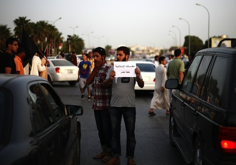 A Libyan follower of Ansar al-Sharia Brigades carries a sign during a protest in front of the Tibesti Hotel, in Benghazi / AP