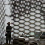 A U.S. Border Patrol agent is seen from Mexico through the fence along the US-Mexico border / AP