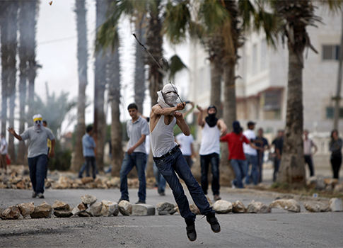 Palestinian hurls stones at Israeli forces during a protest / AP