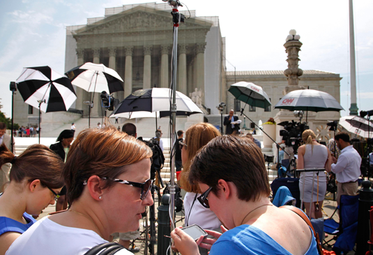 Court watchers and reporters wait outside the U.S. Supreme Court building. REUTERS/Jonathan Ernst