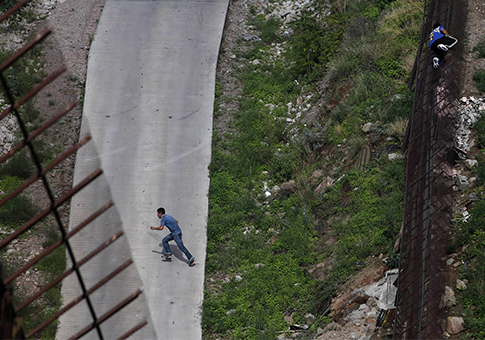 Two men illegally cross the border fence separating Arizona and Mexico / AP