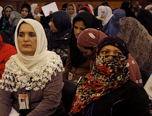 Afghan women listen to President Hamid Karzai, speak during a press conference in Kabul Thursday, May 30, 2013. (AP)