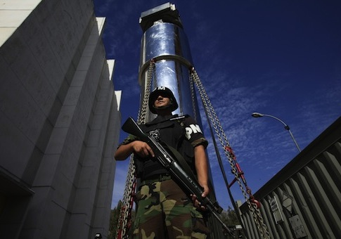 A soldier guards a transport cask containing a transfer cylinder that holds highly enriched uranium / AP