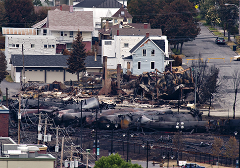 Charred tanker cars are piled up in Lac-Megantic, Quebec / AP