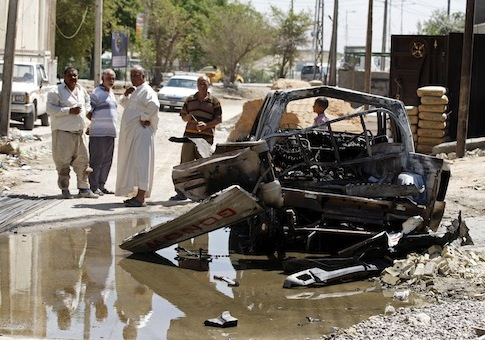 Civilians inspect the aftermath of a car bomb attack in Baghdad, Iraq / AP