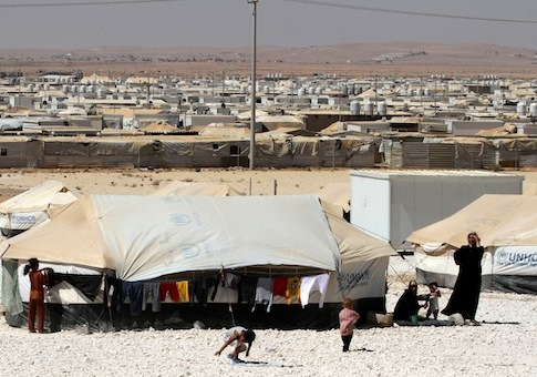 Syrian refugees stand near their tent at Zaatari camp / AP