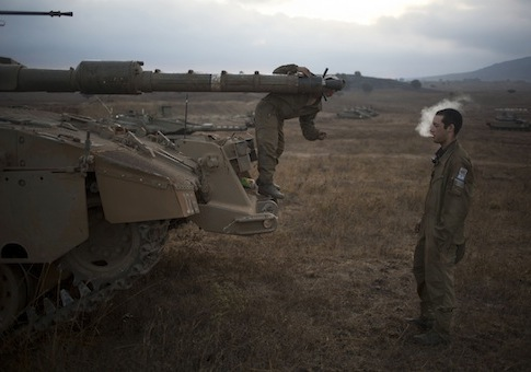 An Israeli soldier checks the barrel of a tank of the 53rd Armor Battalion during an exercise in the Israeli controlled Golan Heights near the border with Syria / AP