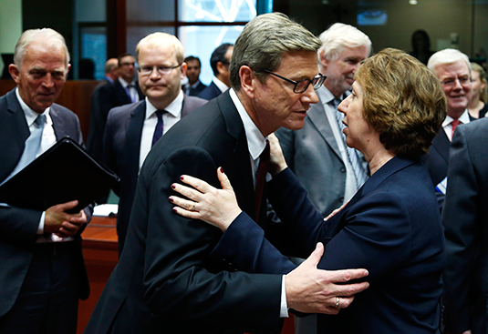 EU Foreign Policy Chief Catherine Ashton (R) greets Germany's Foreign Minister Guido Westerwelle (C) during an emergency EU foreign ministers meeting, Aug. 21, 2013. REUTERS/Francois Lenoir