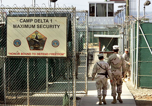 U.S. military guards walk within Camp Delta at Guantanamo Bay in 2006. (AP)