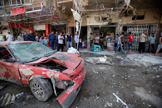 People gather at the site of a car bomb attack in Baghdad's al-Shaab district August 28, 2013. REUTERS/Saad Shalash
