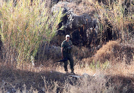 A Palestinian militant of the PFLP stands near a site which PFLP said was hit by an Israeli rocket near a network of tunnels used by the PFLP, Aug. 23, 2013. REUTERS/Mohamed Azakir