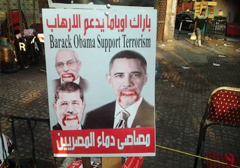"Pro-Army rally sign at Tahrir Square shows Obama, Egyptian President Morsi, and Muslim Brotherhood Supreme Guid Mohamed Badie as ""bloodsuckers of the Egyptians"" / Facebook"