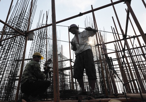 Chinese migrant workers labor at the construction site of a real estate project in Zaozhuang city / AP