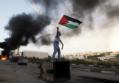 A Palestinian man waves national flag during a protest against Israel's operations in Gaza Strip / AP