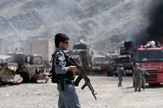 An Afghan policeman stands guard near burning NATO supply trucks following an attack by militants Monday, Sept. 2, 2013. (AP Photo/Rahmat Gul)