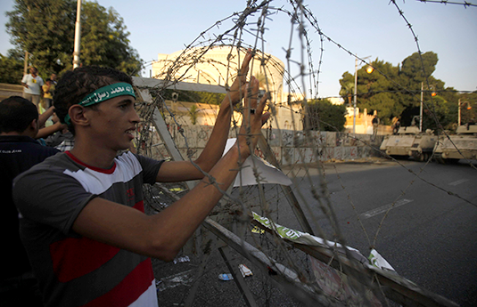 A member of the Muslim Brotherhood and Morsi supporter holds onto barbed wire as he shouts slogans against the military and interior ministry in Cairo Sept. 20, 2013. REUTERS/Amr Abdallah Dalsh