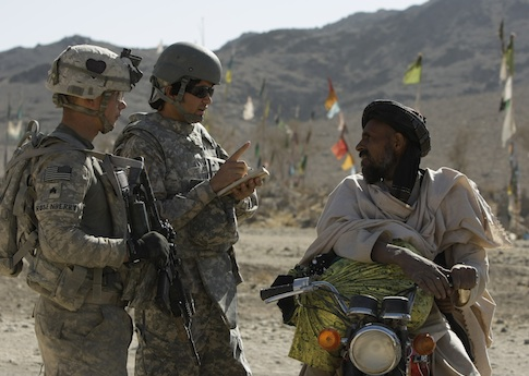 U.S. soldier speaks to Afghani through an interpreter / AP
