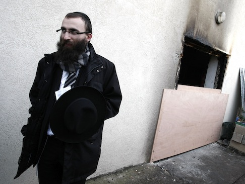 A French Rabbi walks by his synagogue after it was fire-bombed in 2008 / AP