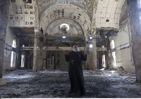Christian Coptic Priest Father Samuel reacts as he stands inside the burned and heavily damaged St. Mousa church in Minya, Egypt / AP