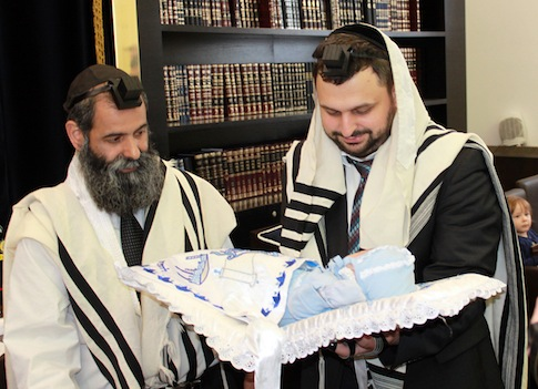 Rabbi Abraham Dauss, left, and  Moishe Furer, a rabbinical student in Berlin holding his son Elchanan attend a circumcision ceremony in Berlin / AP