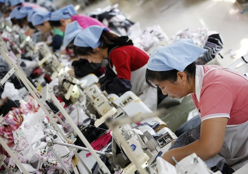 Female Chinese workers sew clothes to be exported to Japan at a factory / AP