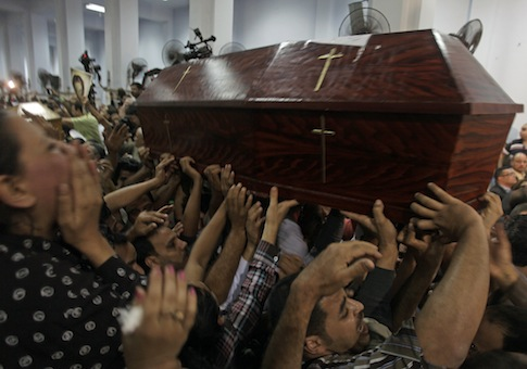Mourners carry the coffin of one of four Copt Christians who were killed late Sunday, during their funeral in Al Warraq's Virgin Mary church in Cairo, Egypt / AP