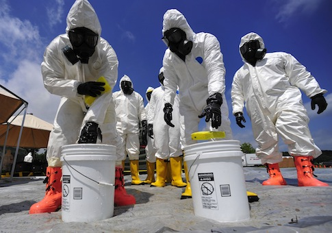 U.S. Soldiers from the 457th Chemical Battalion sponge off their level A protective suits / AP