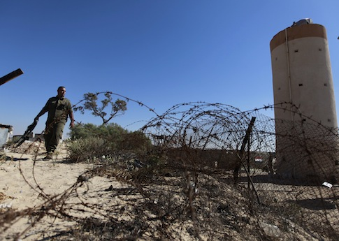 A Palestinian Hamas security guard walks near an Egyptian watch tower on the border with Egypt in Rafah / AP