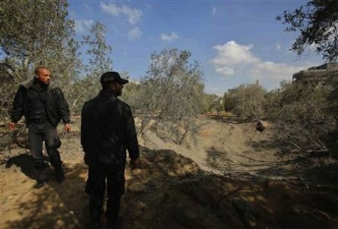 Palestinian policemen loyal to Hamas inspect scene of an Israeli air strike in the Northern Gaza Strip / Reuters