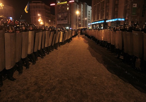 A journalist walks between lines of Ukrainian riot policemen