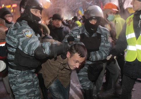 Ukrainian riot policemen pull a Pro-European Union activist out from a tent camp