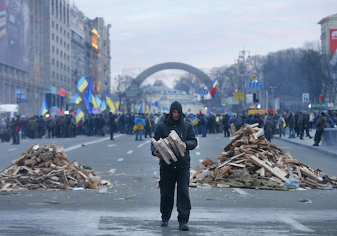 A protester collects firewood for heating in downtown Kiev