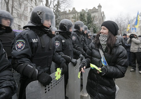 An activist decorates the shields of riot police