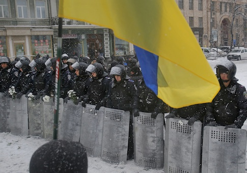 A Ukrainian national flag is waved by pro-European protesters as Ukrainian riot police block the road