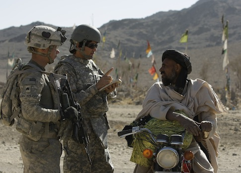 A U.S. soldier with an Afghan interpreter speaking to a local man / AP